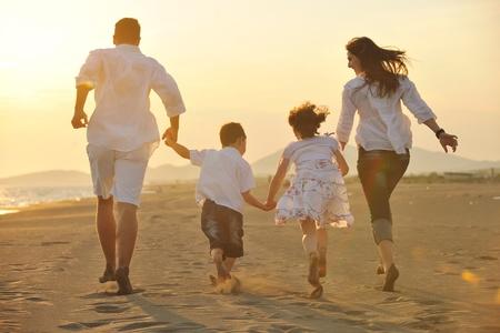 happy young: familia joven feliz divertirse en ejecuci�n de playa y saltar al atardecer
