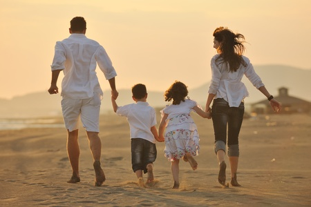 mom and dad: happy young family have fun on beach run and jump  at sunset Stock Photo