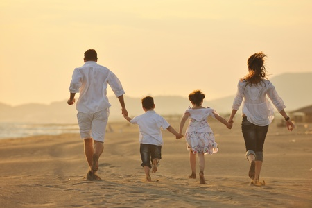 man on beach: happy young family have fun on beach run and jump  at sunset Stock Photo