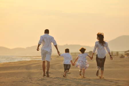 happy young family have fun on beach run and jump  at sunset Stock Photo - 9715707