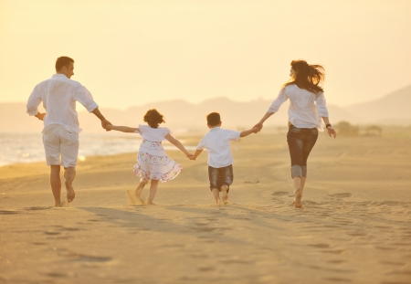 healthy family: happy young family have fun on beach run and jump  at sunset Stock Photo