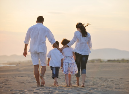 children walking: happy young family have fun on beach run and jump  at sunset Stock Photo
