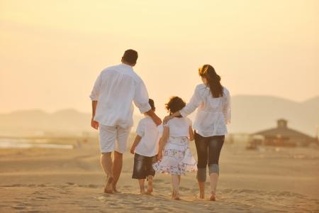 ni�os caminando: joven familia feliz divertirse en ejecuci�n de playa y saltar al atardecer