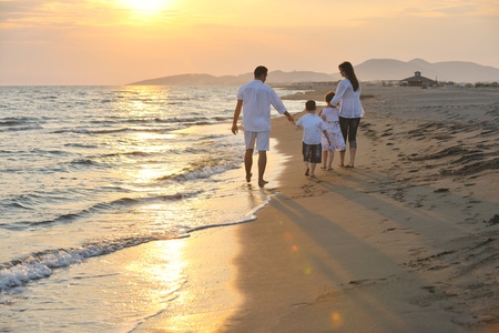 gl?ckliche junge Familie Spa? haben am Strand laufen und springen bei Sonnenuntergang