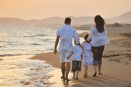 family life: happy young family have fun on beach run and jump  at sunset Stock Photo