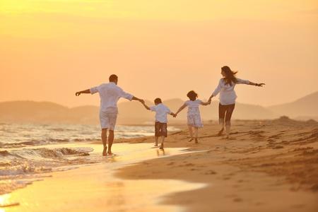 Happy young Family haben Sie Spaß am Strand laufen und springen bei Sonnenuntergang