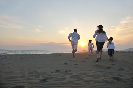 familia joven feliz divertirse en ejecución de playa y saltar al atardecer Foto de archivo