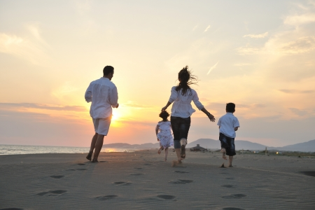 happy young family have fun on beach run and jump  at sunset photo