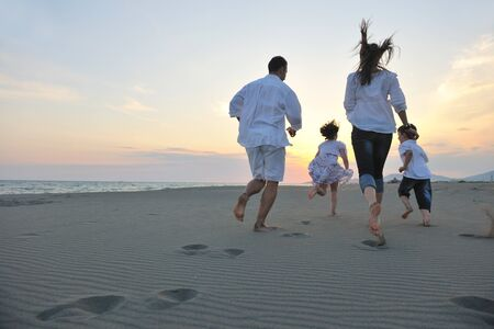 happy young family have fun on beach run and jump  at sunset Stock Photo - 9717916