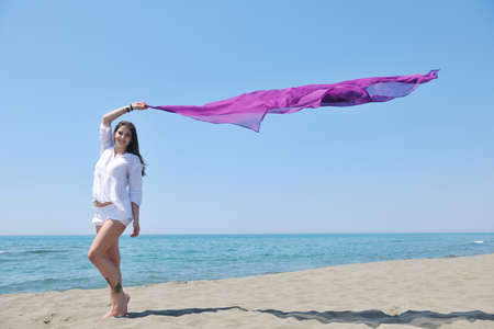 beautiful young woman on beach with scarf relax smile and have fun photo