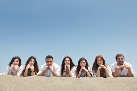 Group of happy young people in circle at beach have fun Stock Photo - 9722397