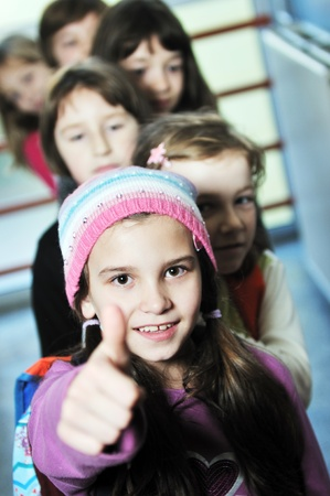 happy school girls posing at corridor with thumbs up photo