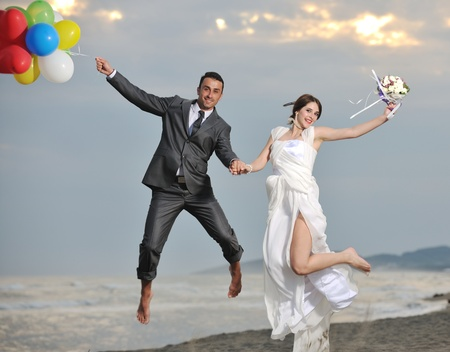 happy just married young couple celebrating and have fun at beautiful beach sunset photo