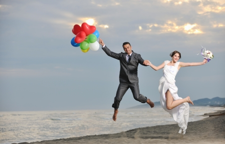 happy just married young couple celebrating and have fun at beautiful beach sunset Stock Photo - 9770580