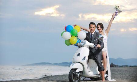 pareja de escena de novios sólo se casó con la boda en la playa paseo scooter blanco y divertirse Foto de archivo