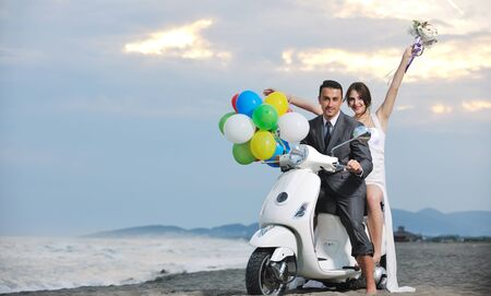 balloon bouquet: wedding scene of bride and groom just married couple on the beach ride white scooter and have fun