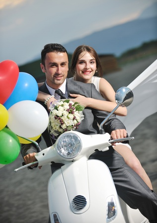 balloon bouquet: wedding sce of bride and groom just married couple on the beach ride white scooter and have fun