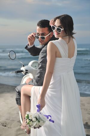 wedding scene of bride and groom just married couple on the beach ride white scooter and have fun photo