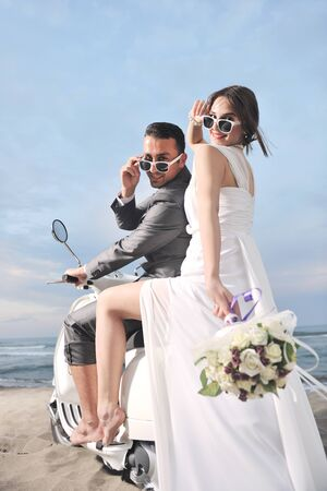 just married: pareja de escena de novios s�lo se cas� con la boda en la playa paseo scooter blanco y divertirse