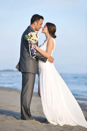 married young couple celebrating and have fun at beautiful beach sunset photo