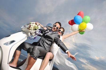 bride and groom on the beach ride a white scooter and have fun photo