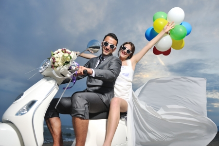 wedding sce of bride and groom just married couple on the beach ride white scooter and have fun Stock Photo - 9781953