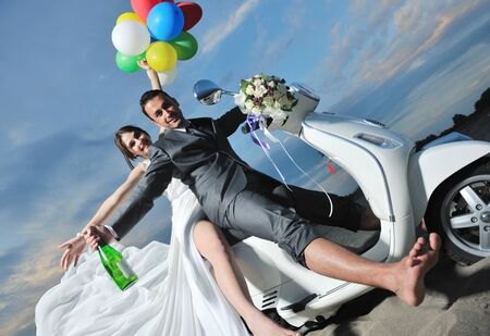 wedding sce of bride and groom just married couple on the beach ride white scooter and have fun Stock Photo - 9872411