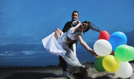 happy just married young couple celebrating and have fun at beautiful beach sunset Stock Photo - 9871392