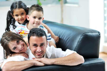 family on couch: happy young family relax and have fun at modern home indooor