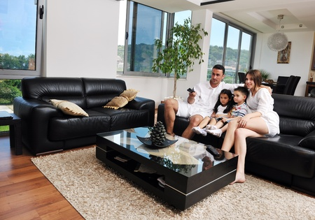 personas viendo television: joven familia feliz wathching tv plana en interiores casa moderna Foto de archivo