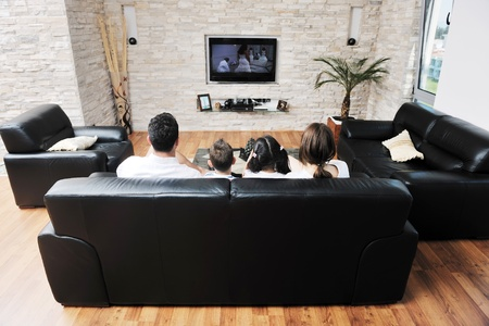 happy young family wathching flat tv at modern home indoor photo