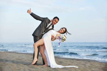 happy just married young couple celebrating and have fun at beautiful beach sunset Stock Photo - 9726308