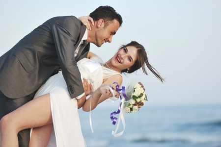 happy just married young couple celebrating and have fun at beautiful beach sunset Stock Photo - 9725773