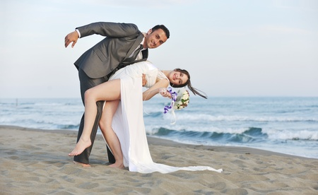 happy just married young couple celebrating and have fun at beautiful beach sunset Stock Photo - 9726209