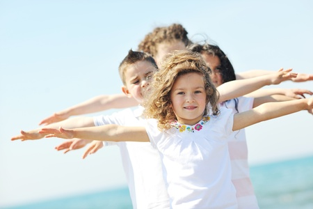 group travel: group of happy child on beach who have fun and play games Stock Photo