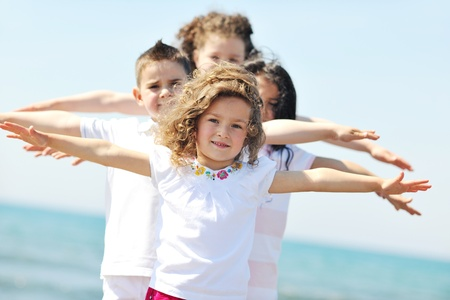 group of happy child on beach who have fun and play games photo