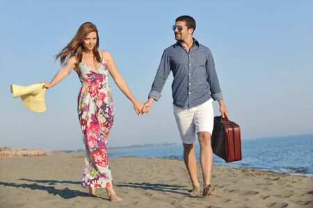 funy: couple on beach with travel bag representing freedom and funy honeymoon concept