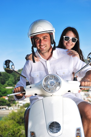 Portrait of happy young love couple on scooter enjoying themselves in a park at summer time photo