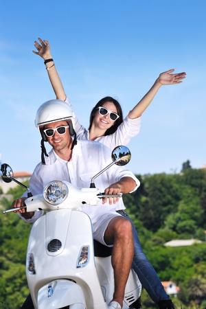vespa: Retrato de amor joven feliz pareja en scooter disfrutando en un parque en el horario de verano Foto de archivo