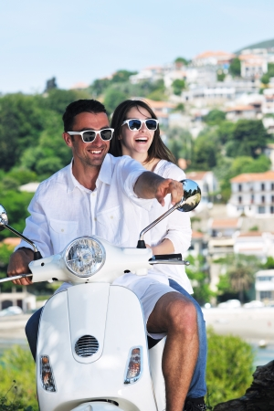 Portrait of happy young love couple on scooter enjoying themselves in a park at summer time Stock Photo - 9948142