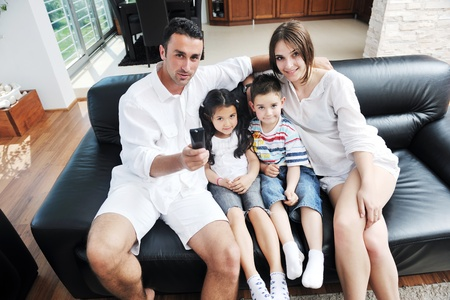 happy young family wathching flat tv at modern home indoor Stock Photo - 9936190