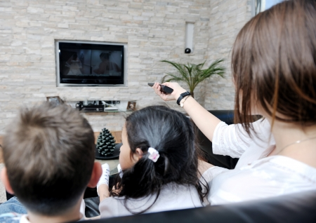 woman watching tv: happy young family wathching flat tv at modern home indoor