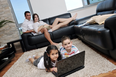 internet love: happy young family have fun and working on laptop at modern  home livingroom indoor