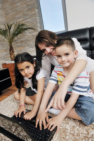 happy young family have fun and working on laptop at modern  home livingroom indoor Stock Photo - 9936347