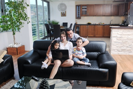 happy young family have fun and working on laptop at modern  home livingroom indoor photo