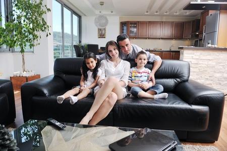 joven familia feliz relajarse y divertirse en indooor hogar moderno Foto de archivo