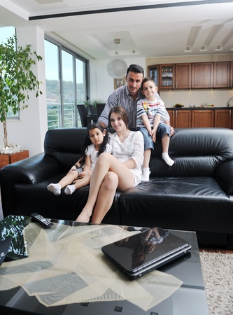 family sofa: happy young family relax and have fun at modern home indooor