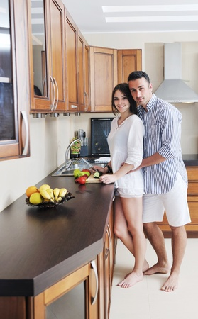 family in kitchen: happy young couple have fun in modern wooden  kitchen indoor while preparing fresh food