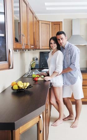 novio: joven pareja feliz se divierten en la cubierta moderna cocina de madera, mientras que la preparación de los alimentos frescos