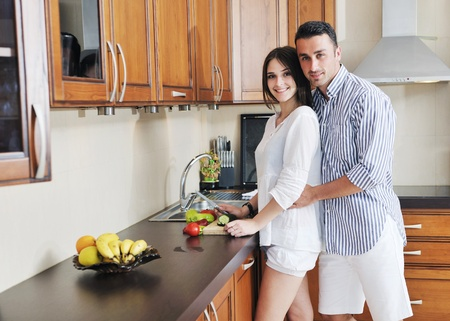 happy young couple have fun in modern wooden  kitchen indoor while preparing fresh food Stock Photo - 9942978
